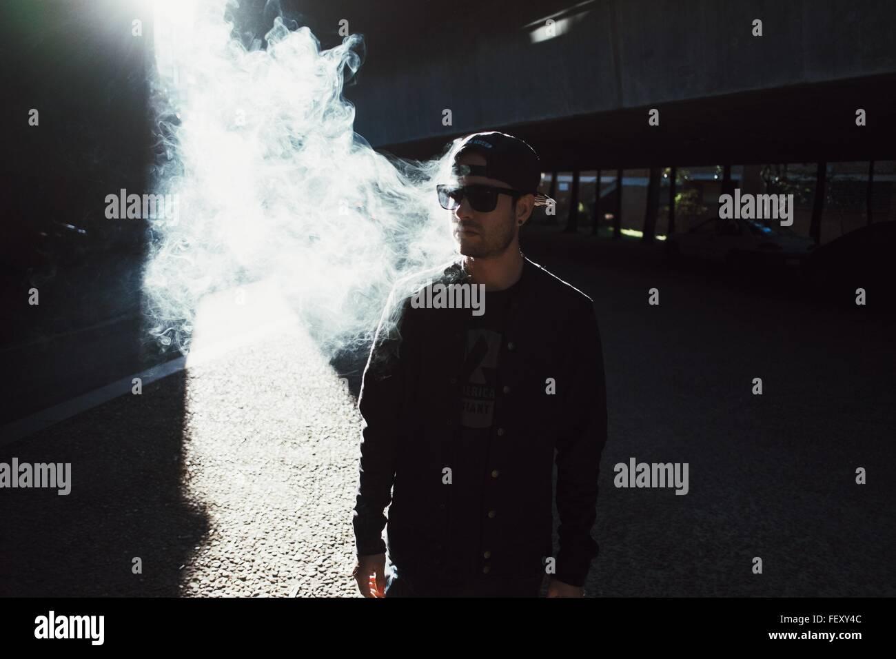 Young Man Smoking Cigarette On Street - Stock Image