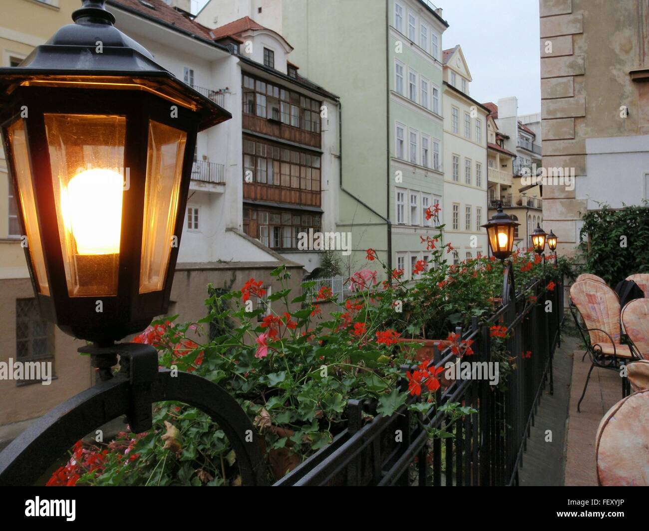 Illuminated Electric Lamp On Fence Outside Buildings - Stock Image