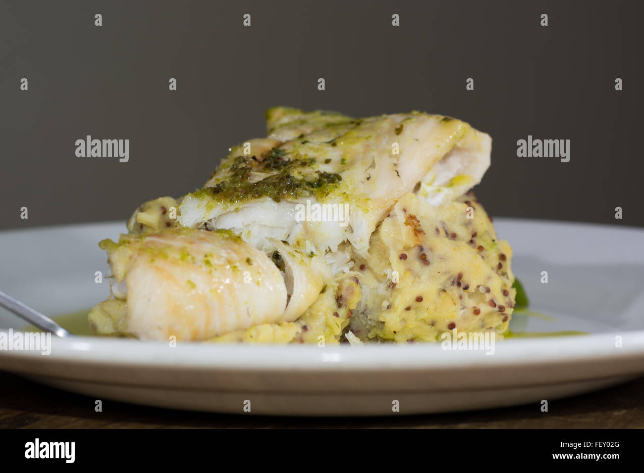 Haddock with whole grain mash and garlic parsley butter. French restaurant prepared fish dish with mashed potato Stock Photo
