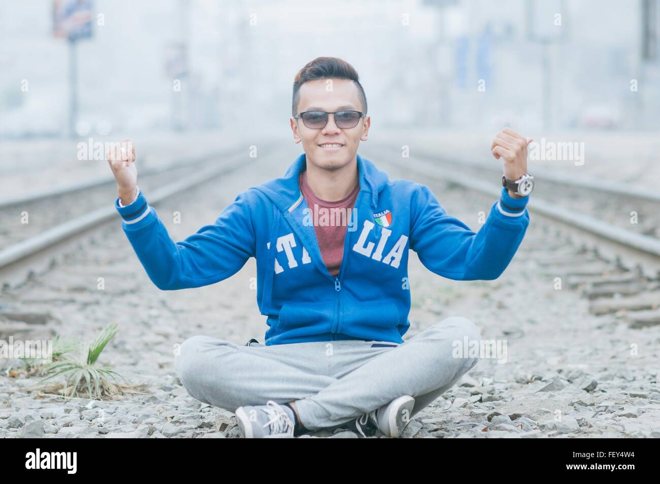 Portrait Of Smiling Man Gesturing While Sitting Amidst Railroad Tracks On Field - Stock Image