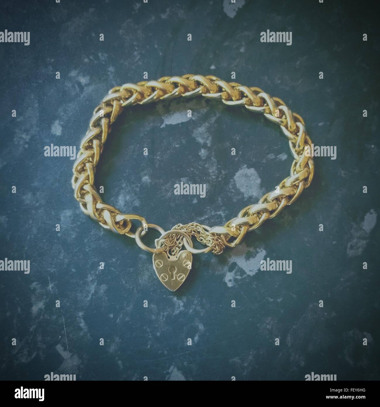 High Angle View Of Gold Bracelet On Granite - Stock Image