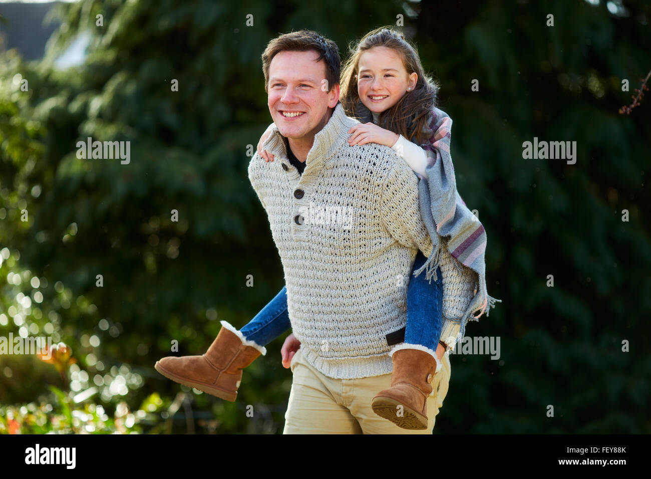 Father giving daughter piggyback Stock Photo