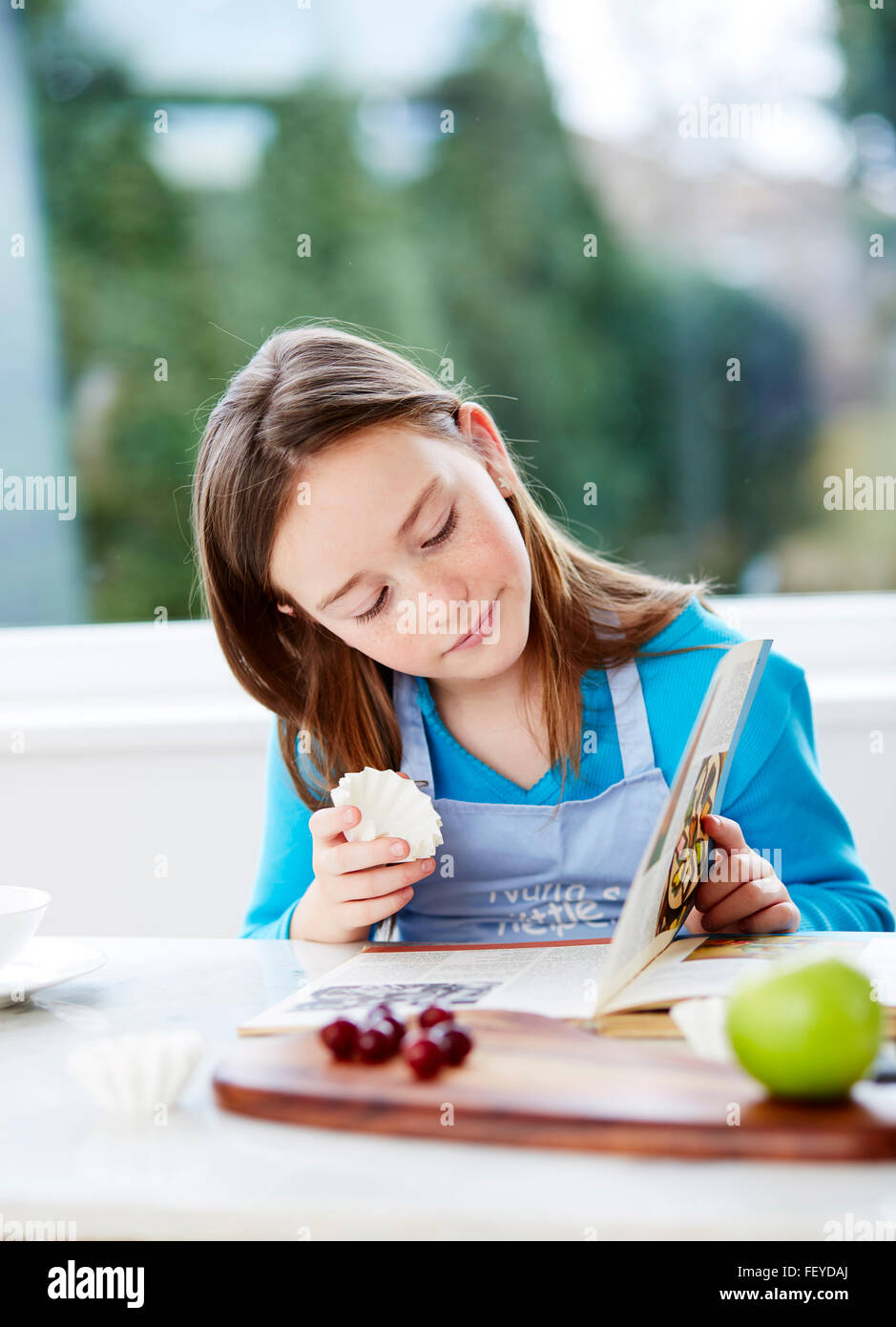Child looking through recipe book - Stock Image