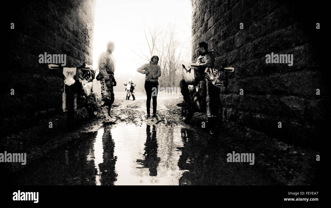 Woman Standing Amidst Bikers In Tunnel - Stock Image