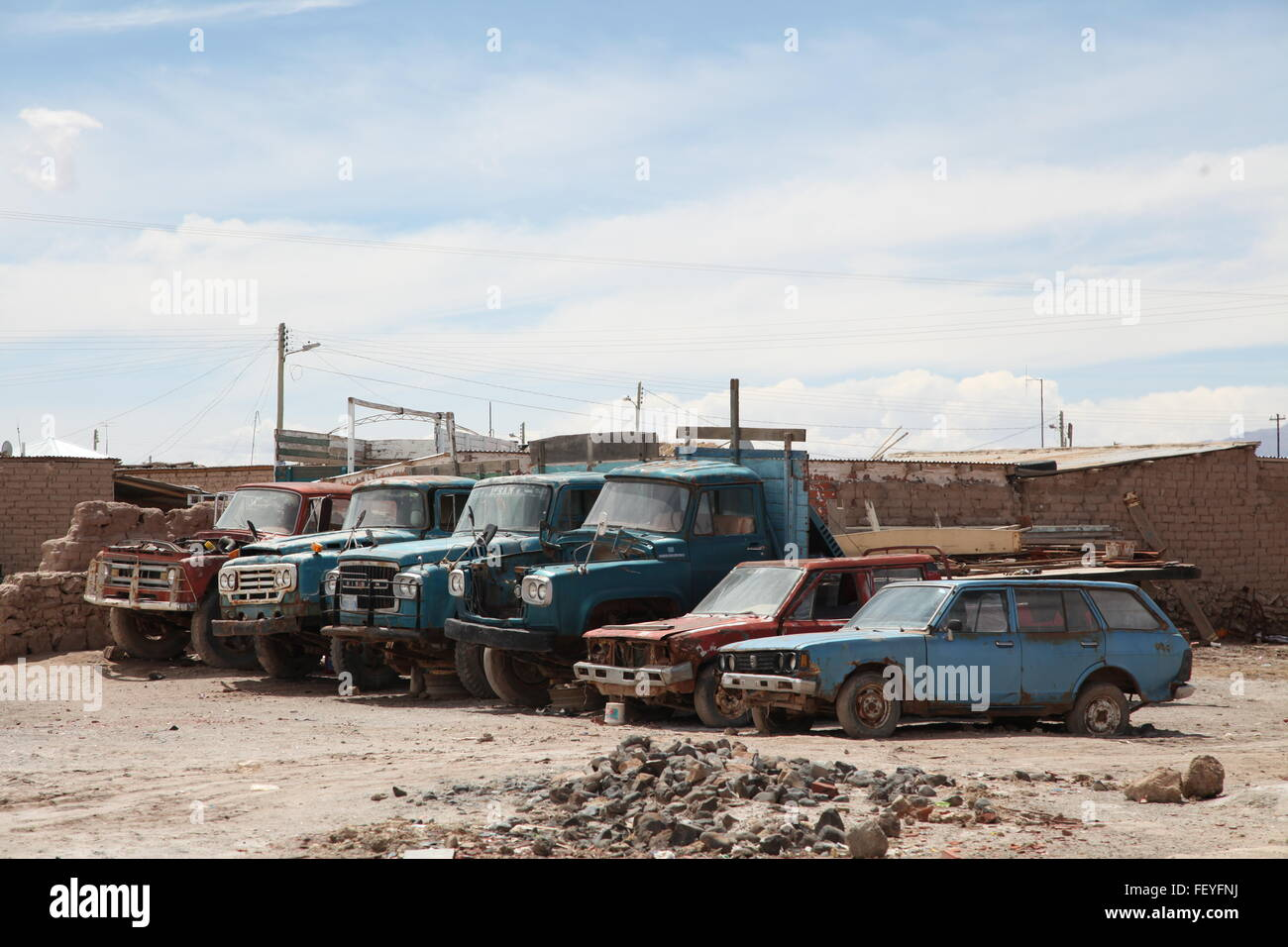 Vehicles In Junkyard Against Cloudy Sky - Stock Image
