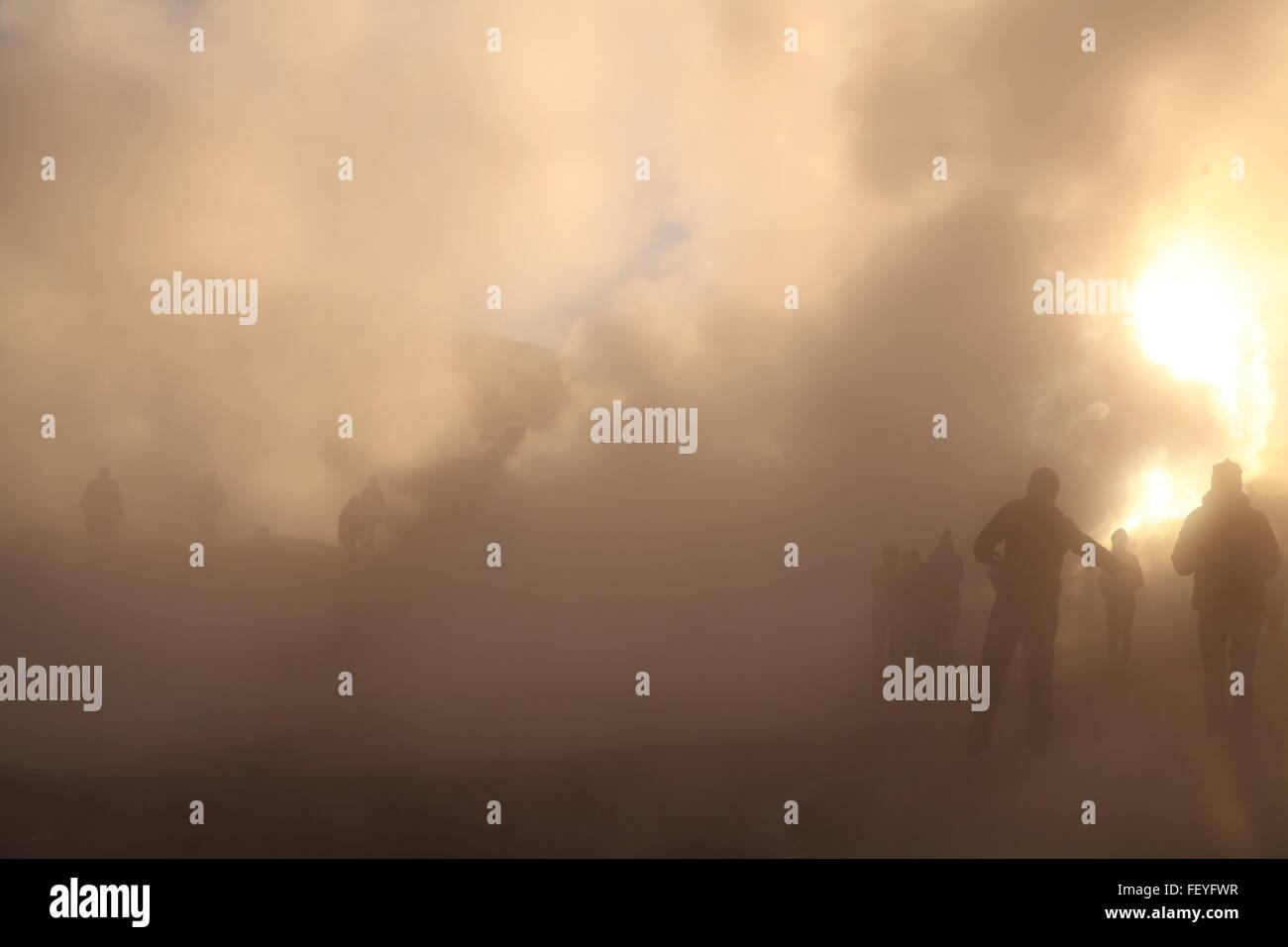 Tourists Walking Through Steam Rising From Geyser At Salar De Uyuni - Stock Image