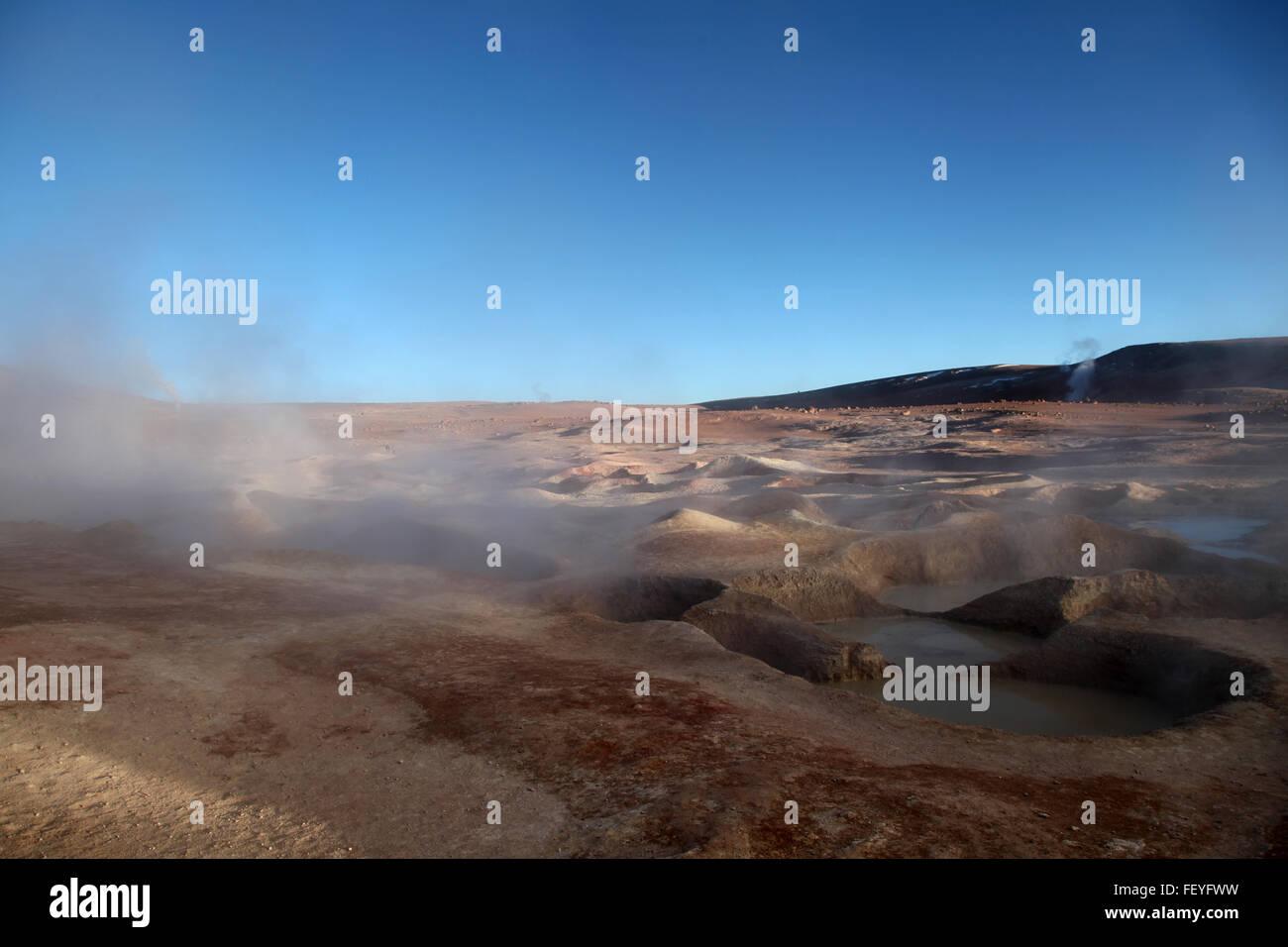 Steam Rising From Geyser At Salar De Uyuni Against Blue Sky - Stock Image