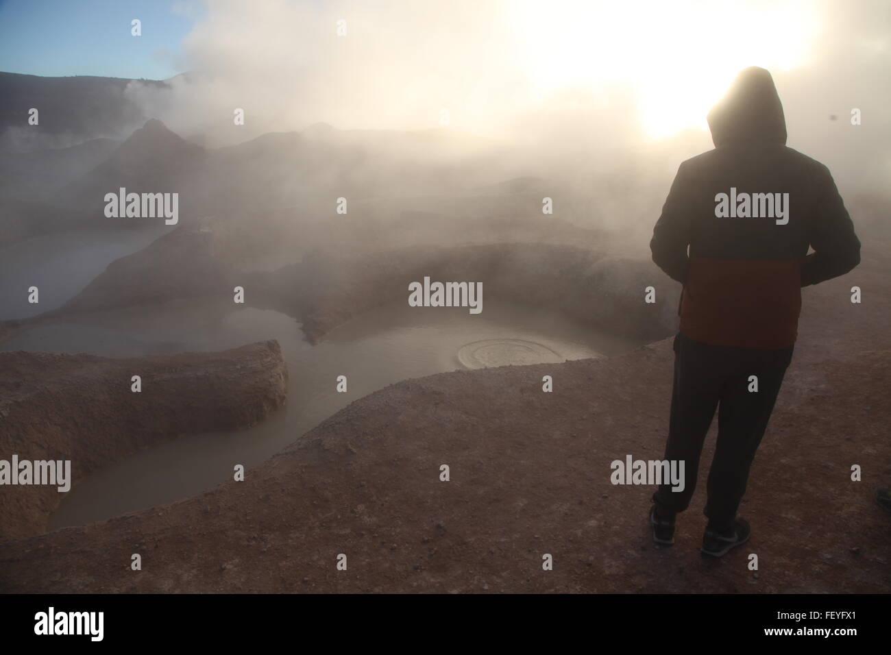 Tourist Watching Steam Rising From Geyser At Salar De Uyuni - Stock Image