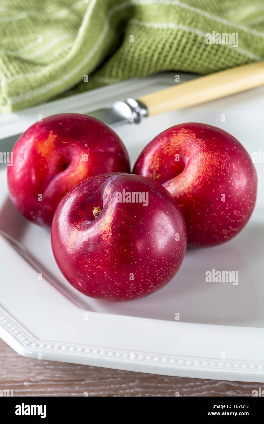 three nectarines on a white plate - Stock Image