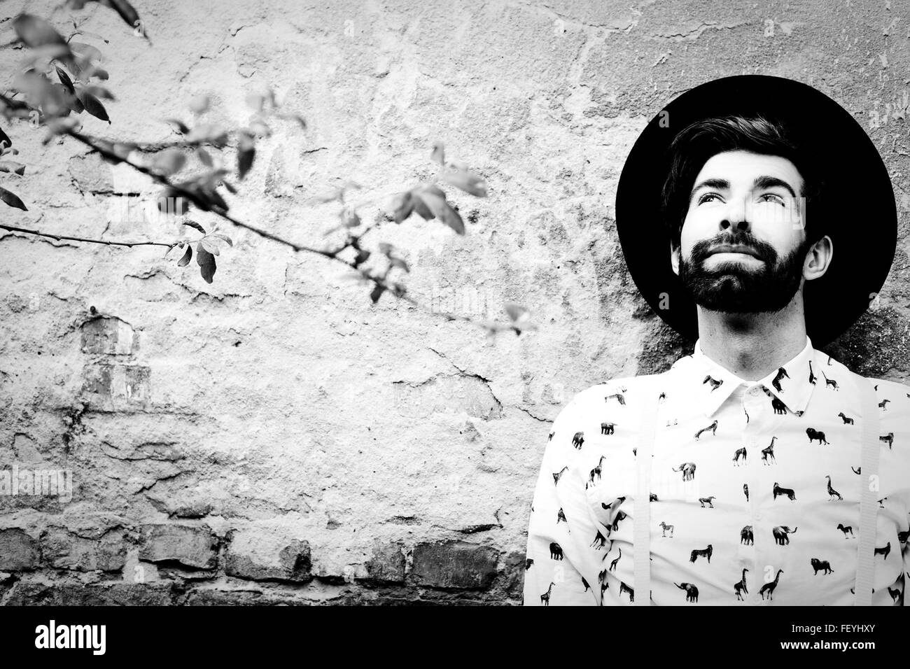 Young Man With Beard And Hat Against Wall - Stock Image