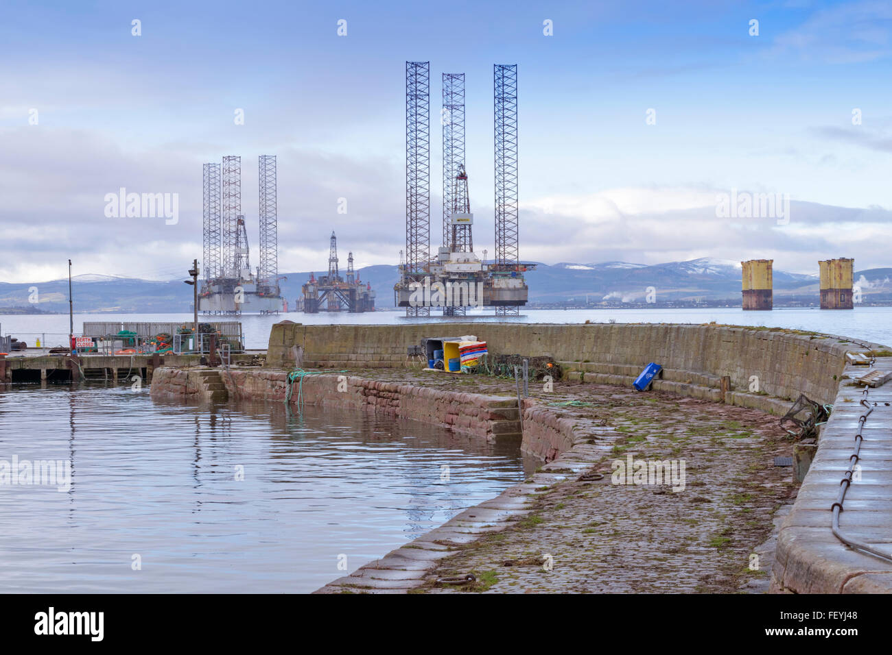 CROMARTY HARBOUR WALLS WITH NORTH SEA OIL RIGS ANCHORED IN THE FIRTH BLACK ISLE SCOTLAND - Stock Image