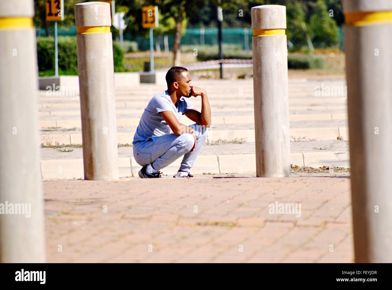 Young Man Crouching While Contemplating On Street - Stock Image