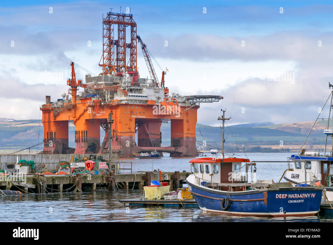 NORTH SEA OIL RIG WEST PHOENIX TOWERS OVER FISHING BOATS MOORED IN CROMARTY HARBOUR CROMARTY FIRTH SCOTLAND Stock Photo