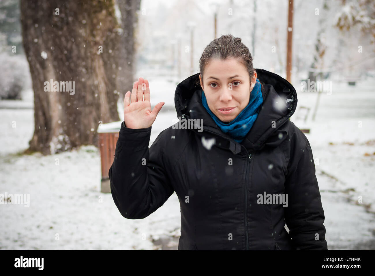 Woman taking an oath in a park in falling snow - Stock Image