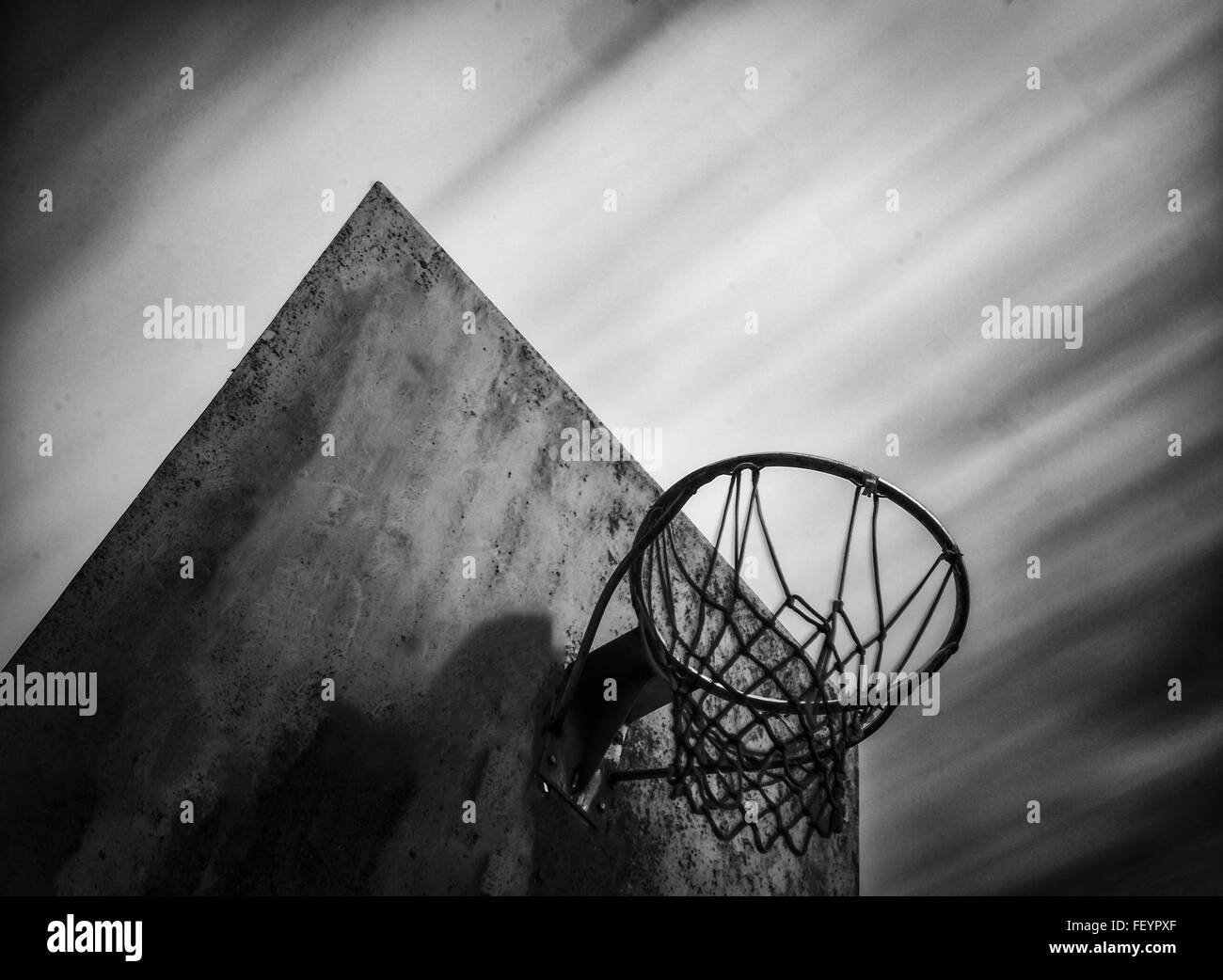 Long exposure of old abandoned basketball in black and white in a cloudy day stock
