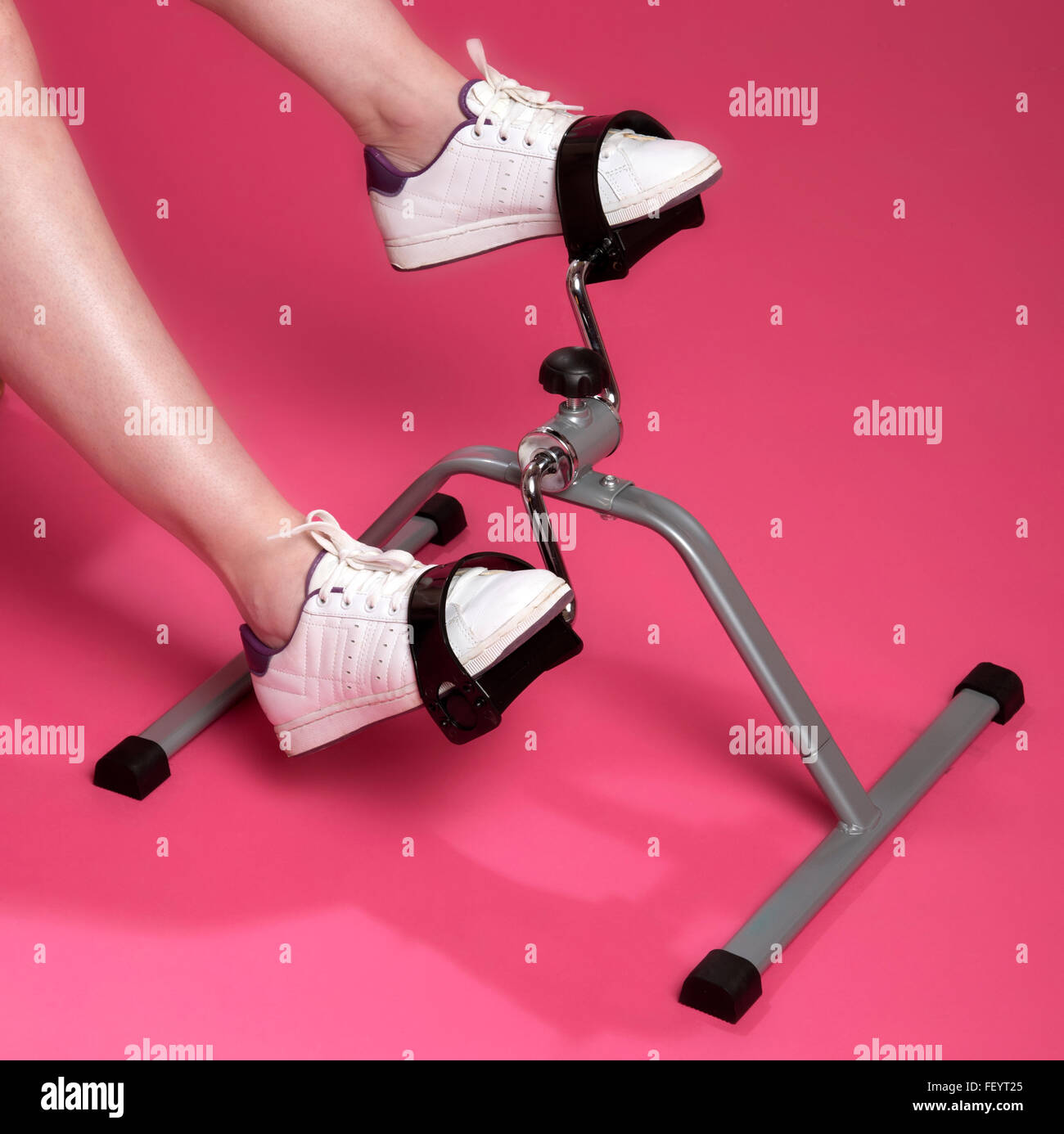 Exercising feet and ankles using an exercise machine Wearing trainers - Stock Image