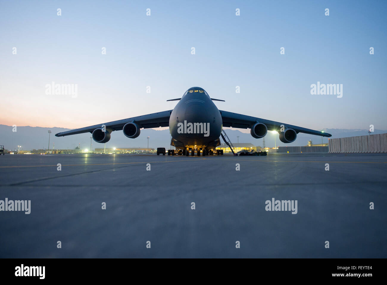 A C-5 Galaxy from Travis Air Force Base, Calif., sits on the ramp as the sun sets prior to a sortie at Bagram Air - Stock Image