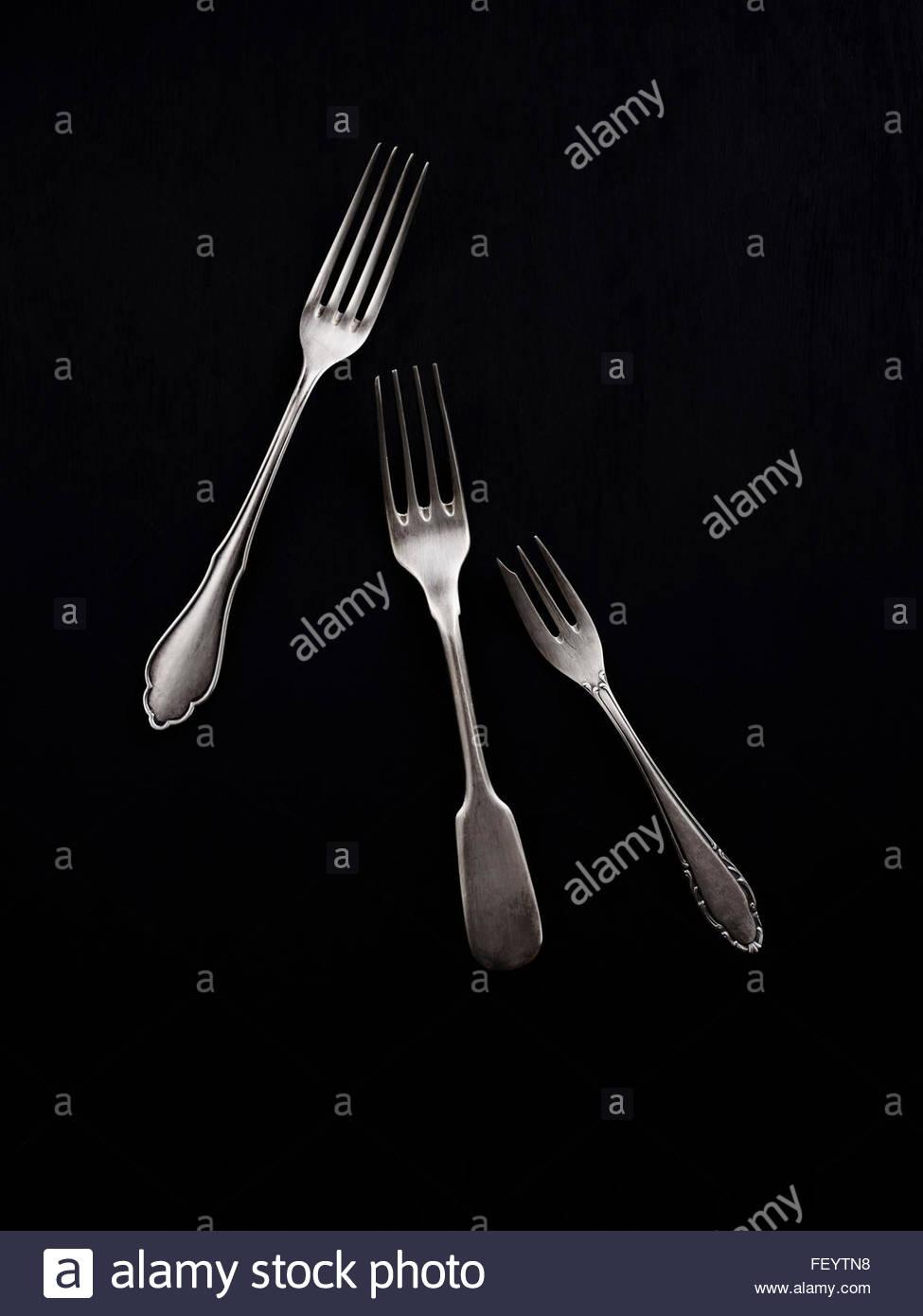 Three antique forks on black background - Stock Image