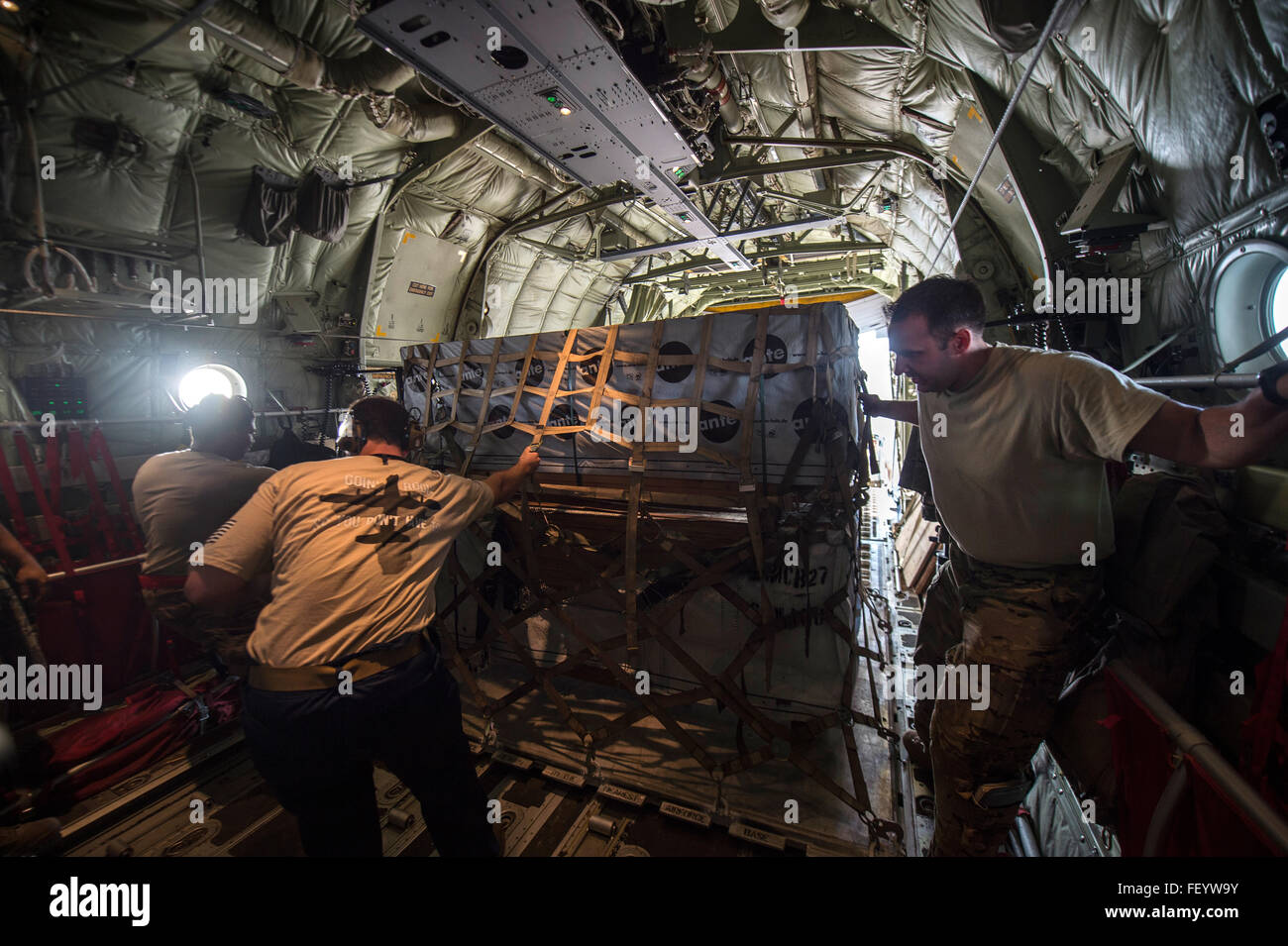 U.S. Air Force loadmasters from the 75th Expeditionary Airlift Squadron load cargo into a C-130 Hercules at Camp - Stock Image