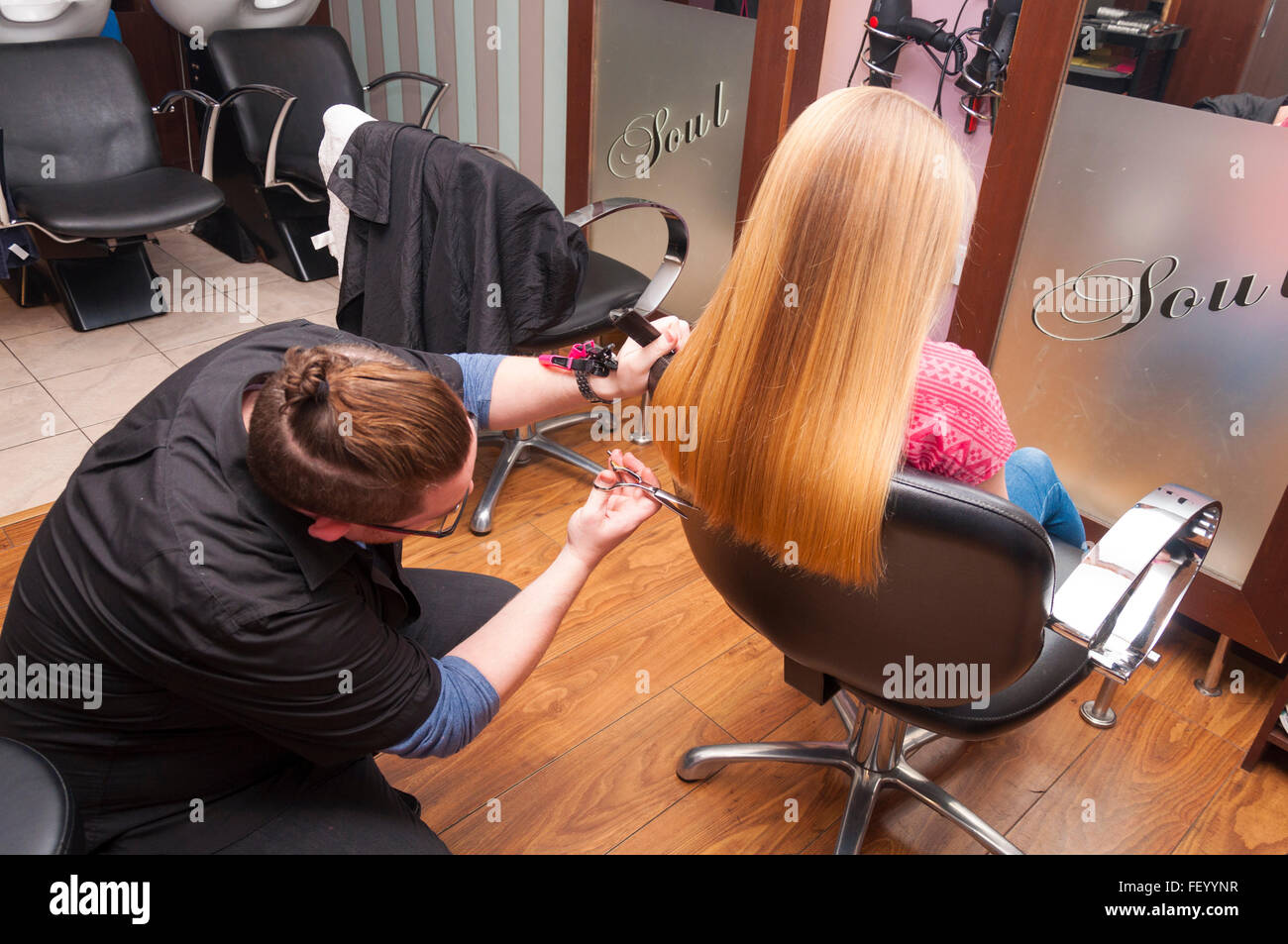 Girl having a haircut in a salon - Stock Image