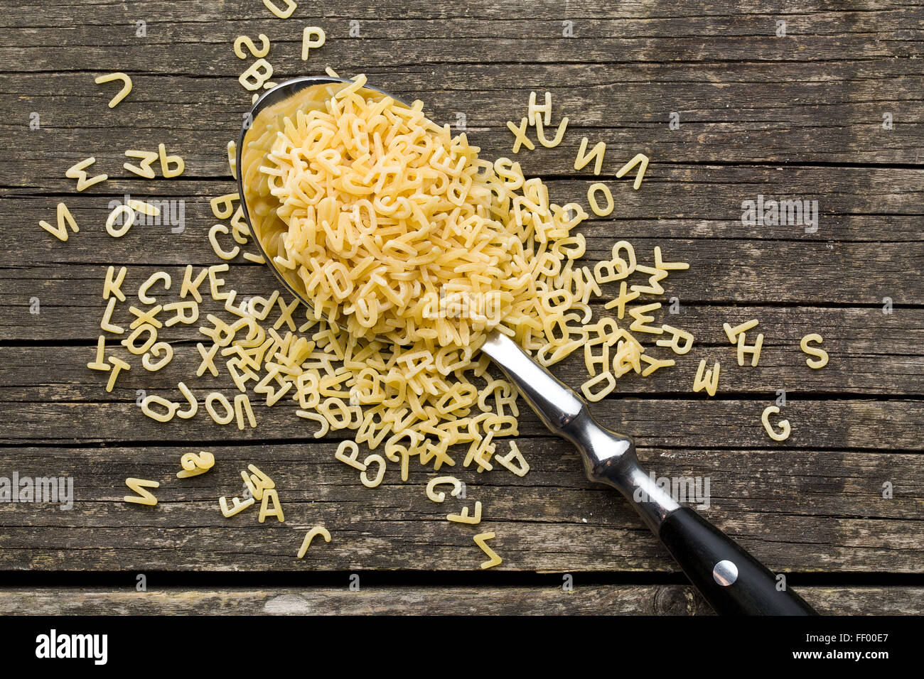 alphabet pasta in spoon on old wooden table - Stock Image