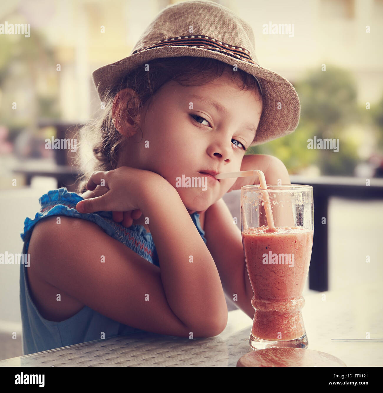 Clever serious kid girl drinking vitamin smoothie juice in street cafe and looking. Toned closeup portrait - Stock Image