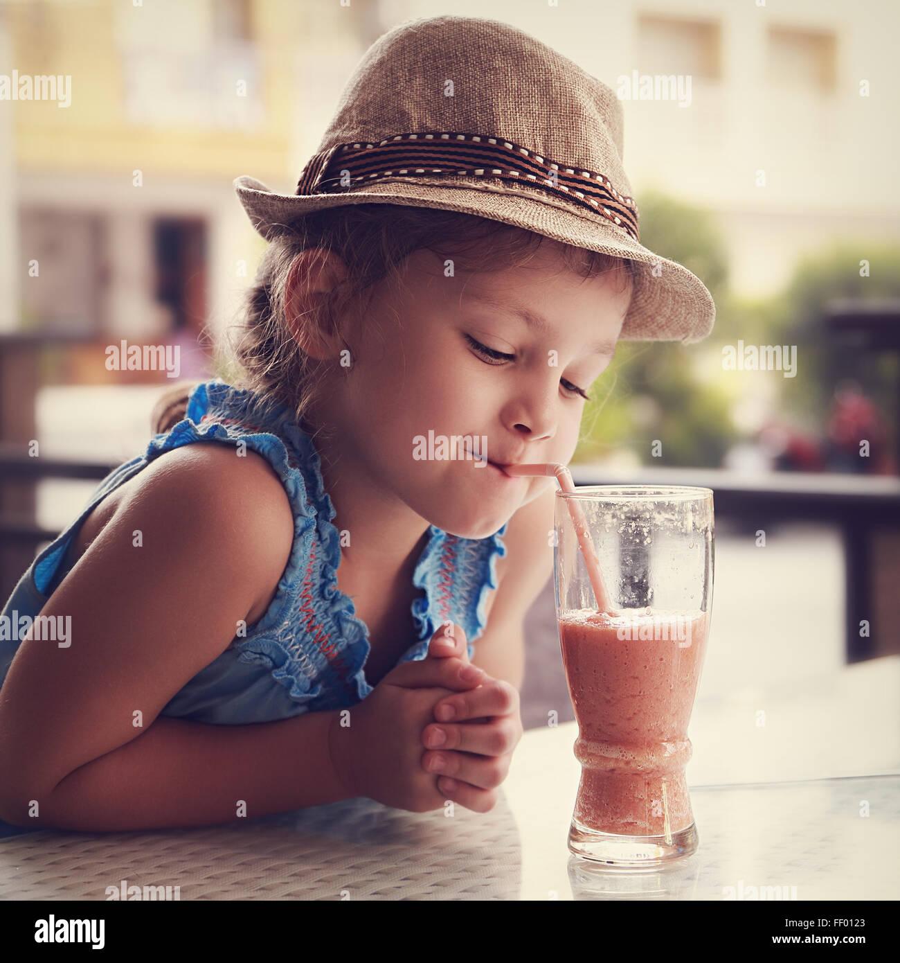 Cute thinking kid girl drinking tasty juice in street restaurant. Toned closeup portrait - Stock Image