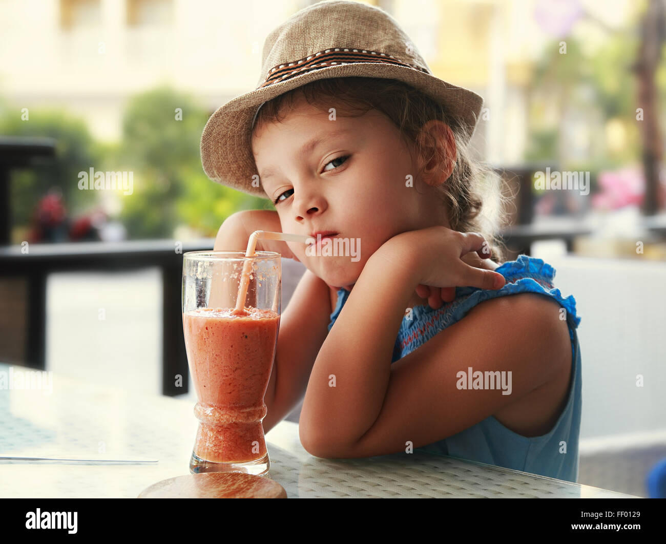 Clever serious kid girl drinking vitamin smoothie juice in street cafe and looking Stock Photo