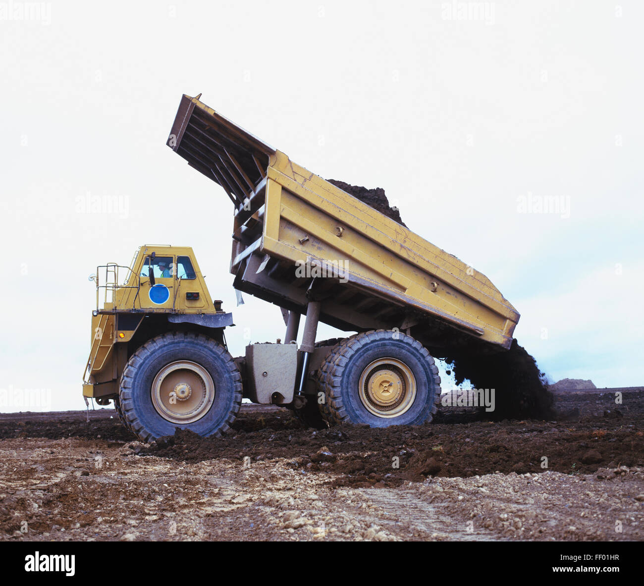 Tipper truck dumping load, side view - Stock Image
