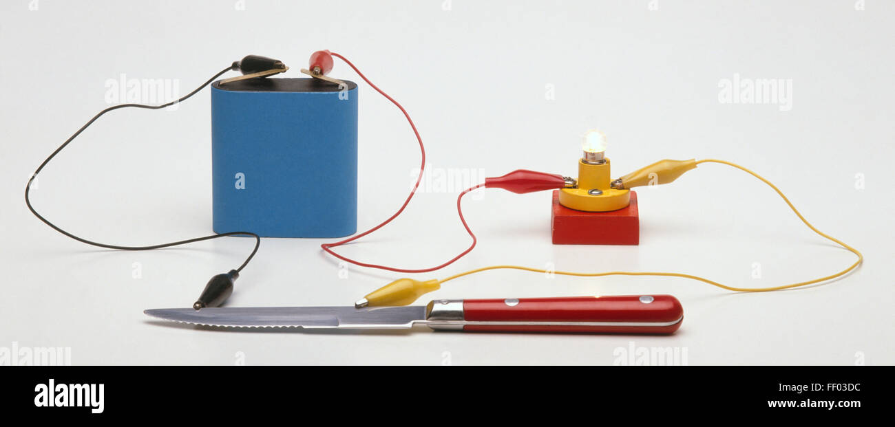 Testing for conductivity using a battery connected by a lead to a small light bulb, a lead leading from the battery - Stock Image
