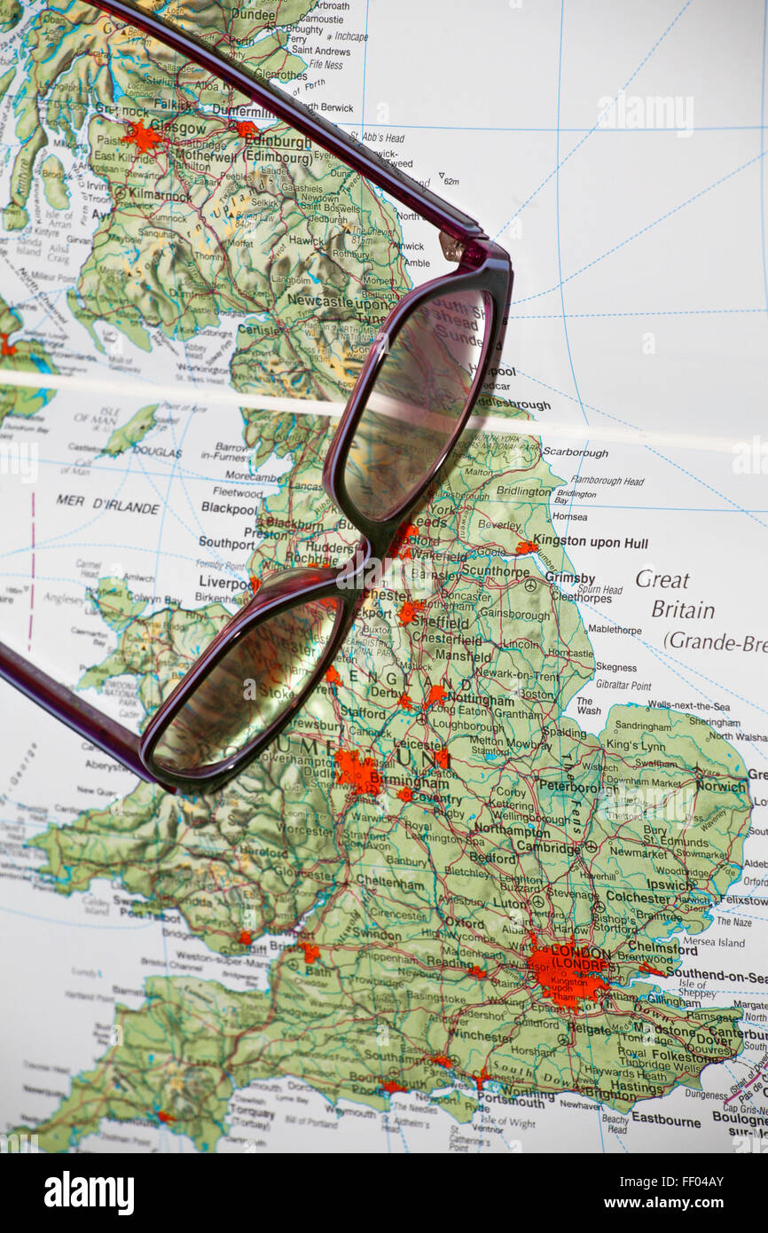 Glasses laying on a open geographical atlas book, close-up