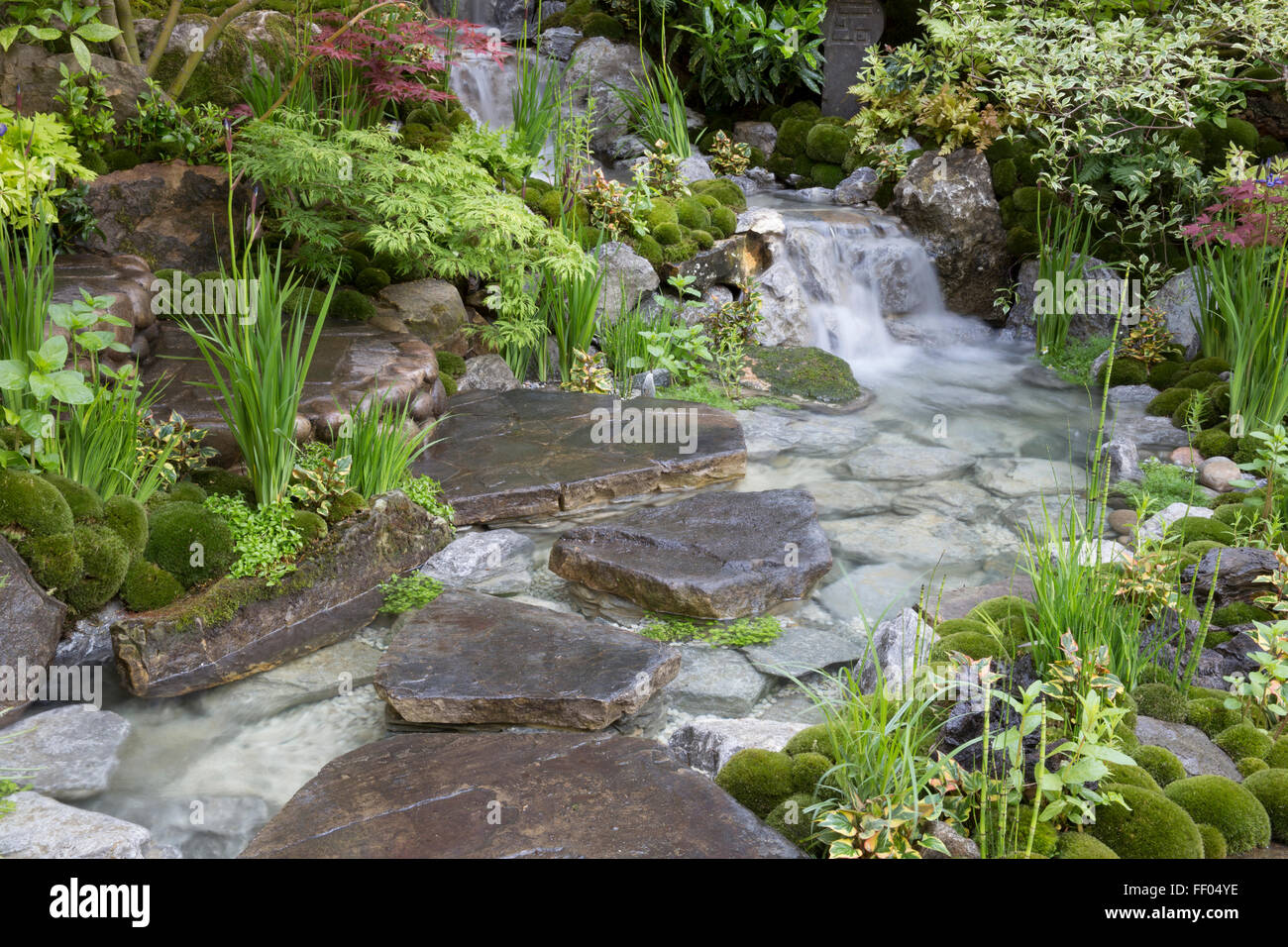 Edo no Niwa – Edo Garden – Japanese garden with waterfall water feature stone stepping stones, moss covered stone - Stock Image