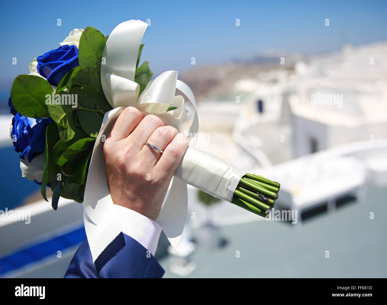 Man's hand holding wedding bouquet on a background of white buildings - Stock Image