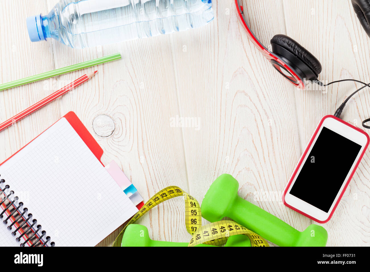 Health and fitness concept. Dumbbells, water bottle, smartphone, headphones and notepad. Top view with copy space - Stock Image