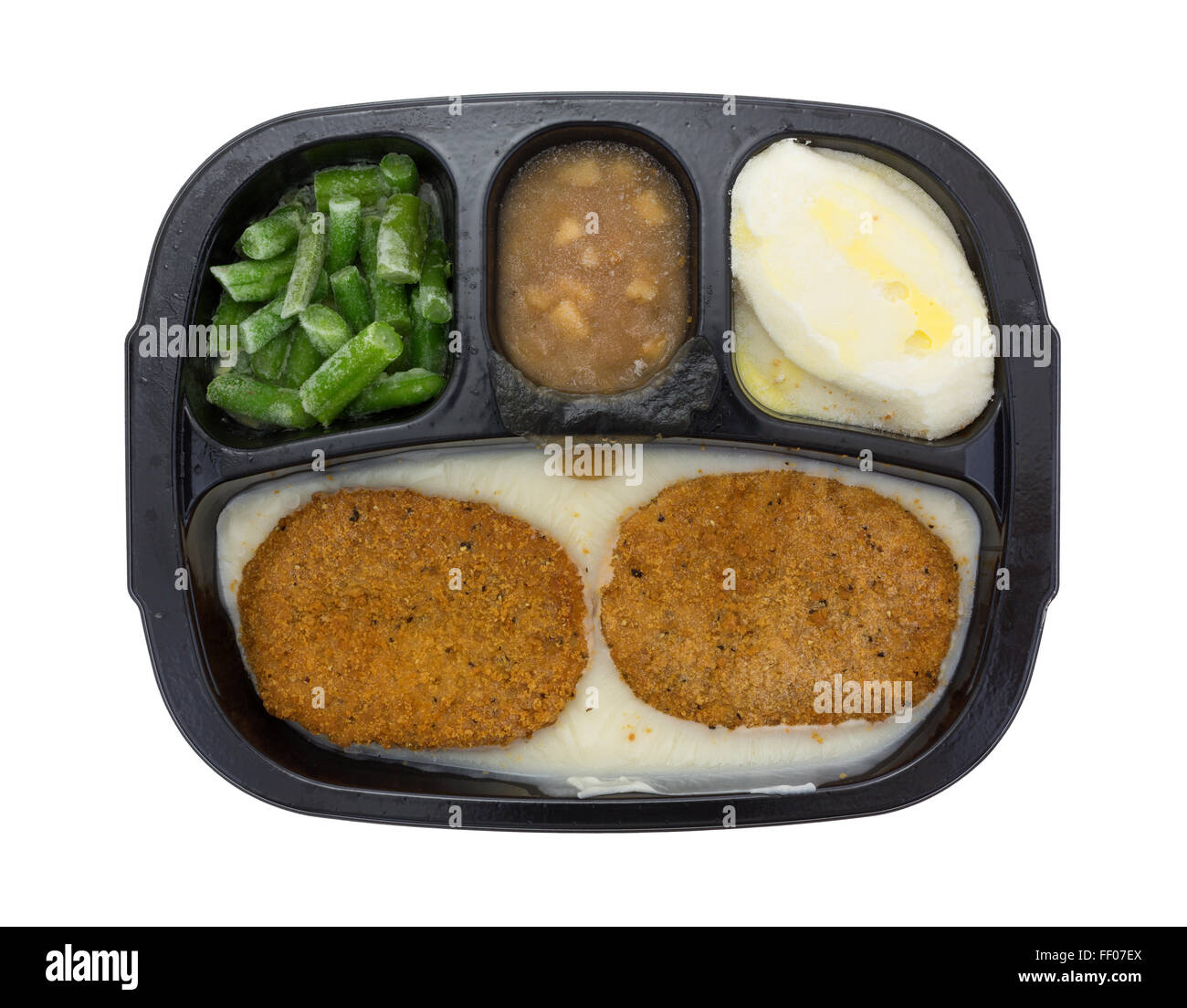 Top view of a frozen fried chicken patties TV dinner with potatoes, green beans and apples in sauce on a white background. - Stock Image