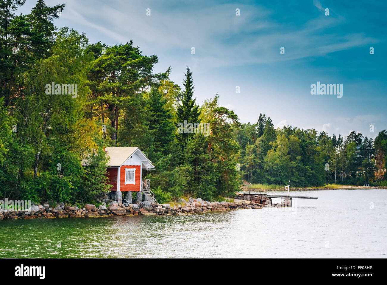 Red Finnish Wooden Sauna Log Cabin On Island In Summer - Stock Image
