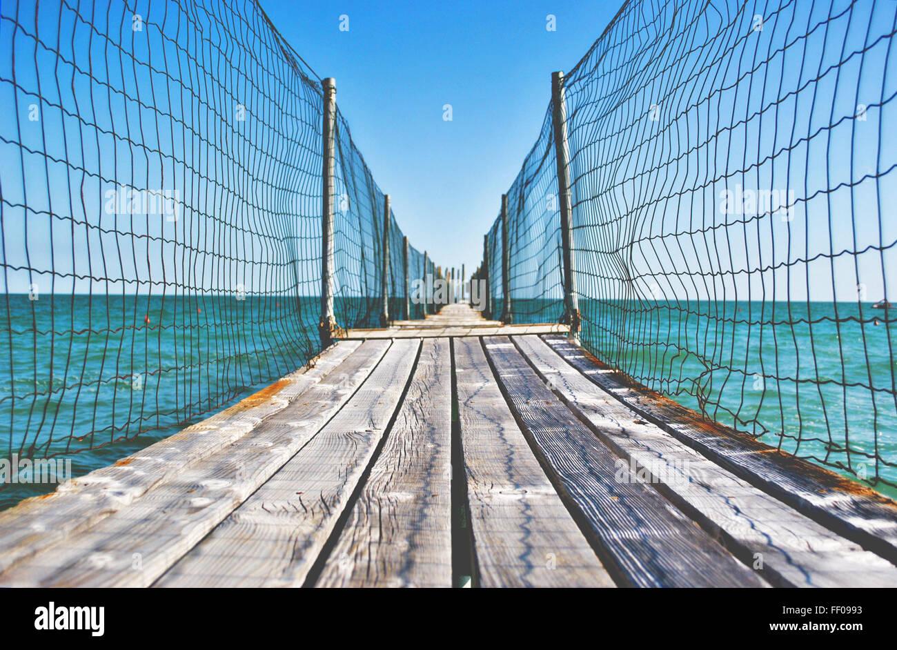 Fenced Wooden Boardwalk Over Ocean Fenced Wooden Boardwalk Over Ocean - Stock Image
