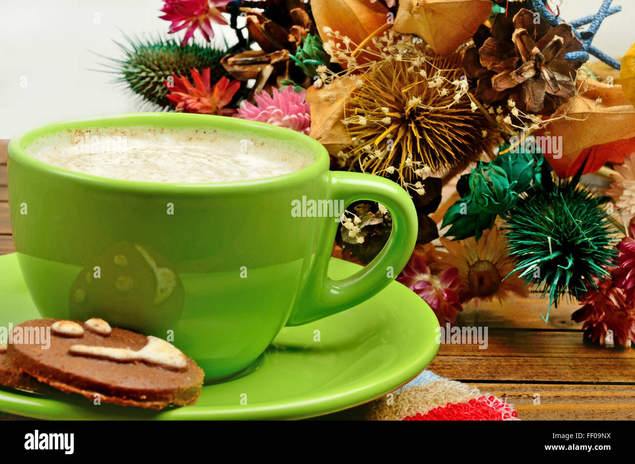 Cup of cappuccino and dried flower decoration on wooden table - Stock Image