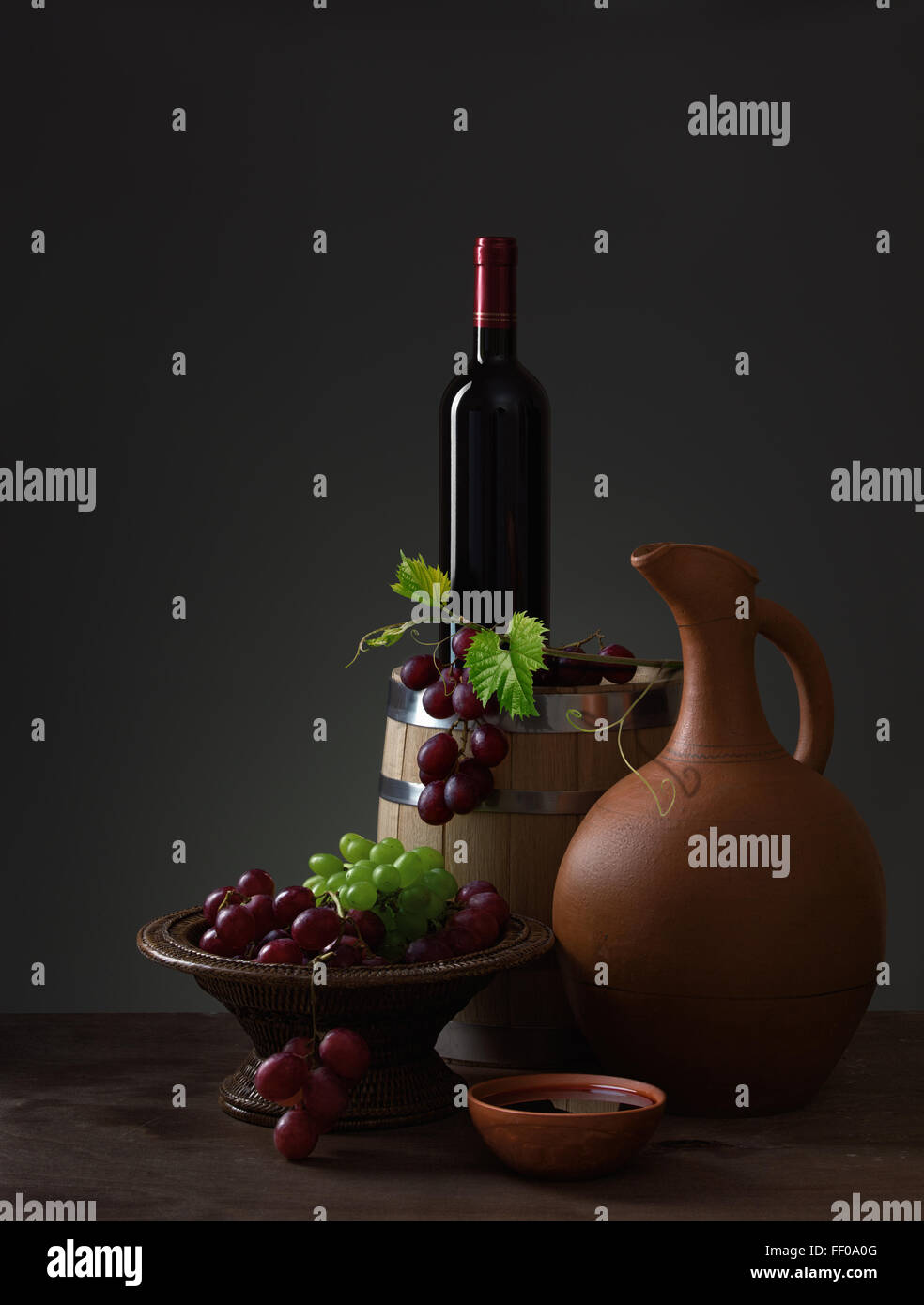 Bottle of red wine, pitcher, grapes and wooden barrel - Stock Image
