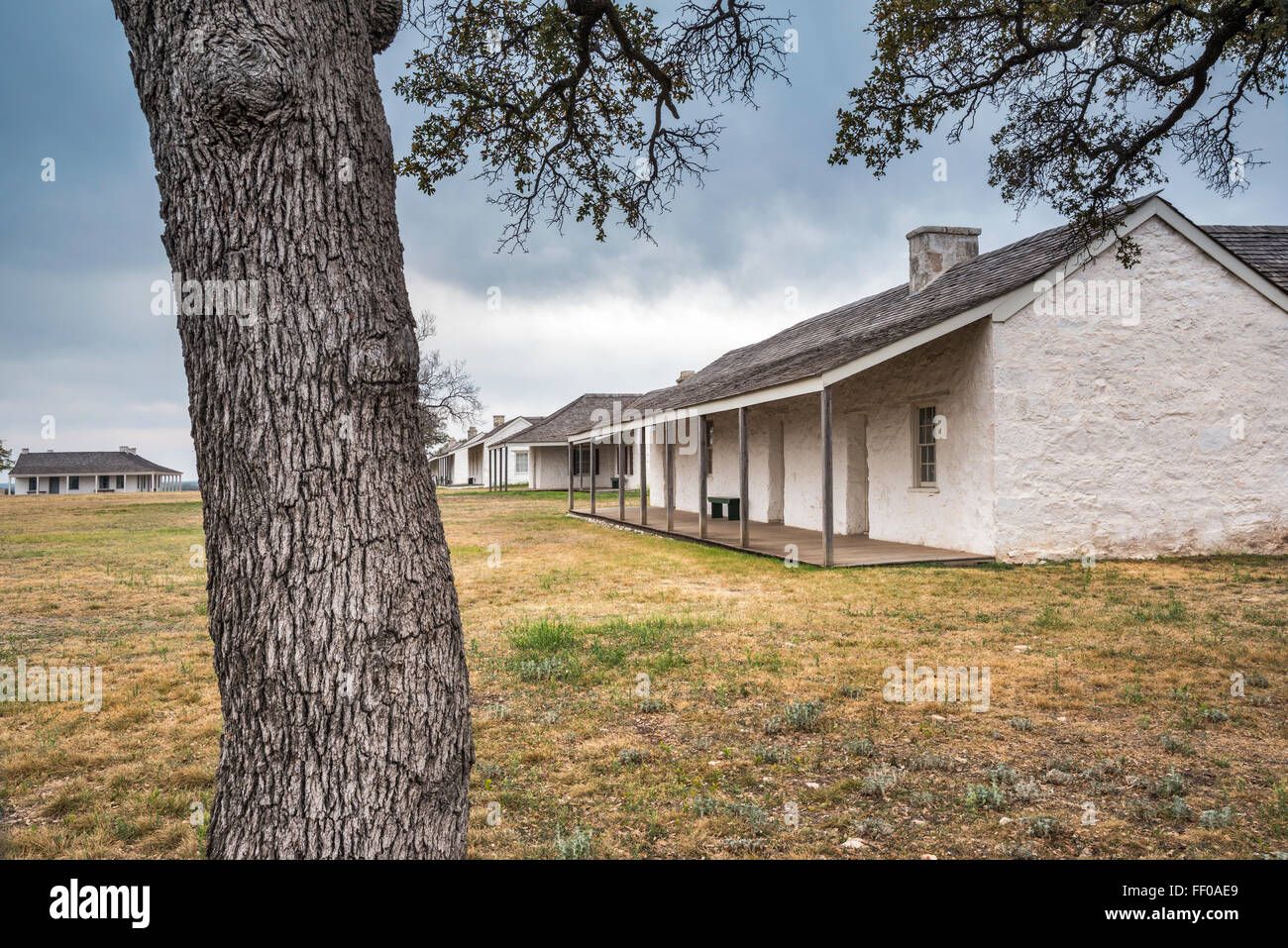 Lieutenants Row reconstructed buildings, live oak tree trunk at Fort McKavett State Historic Site in Fort McKavett, - Stock Image