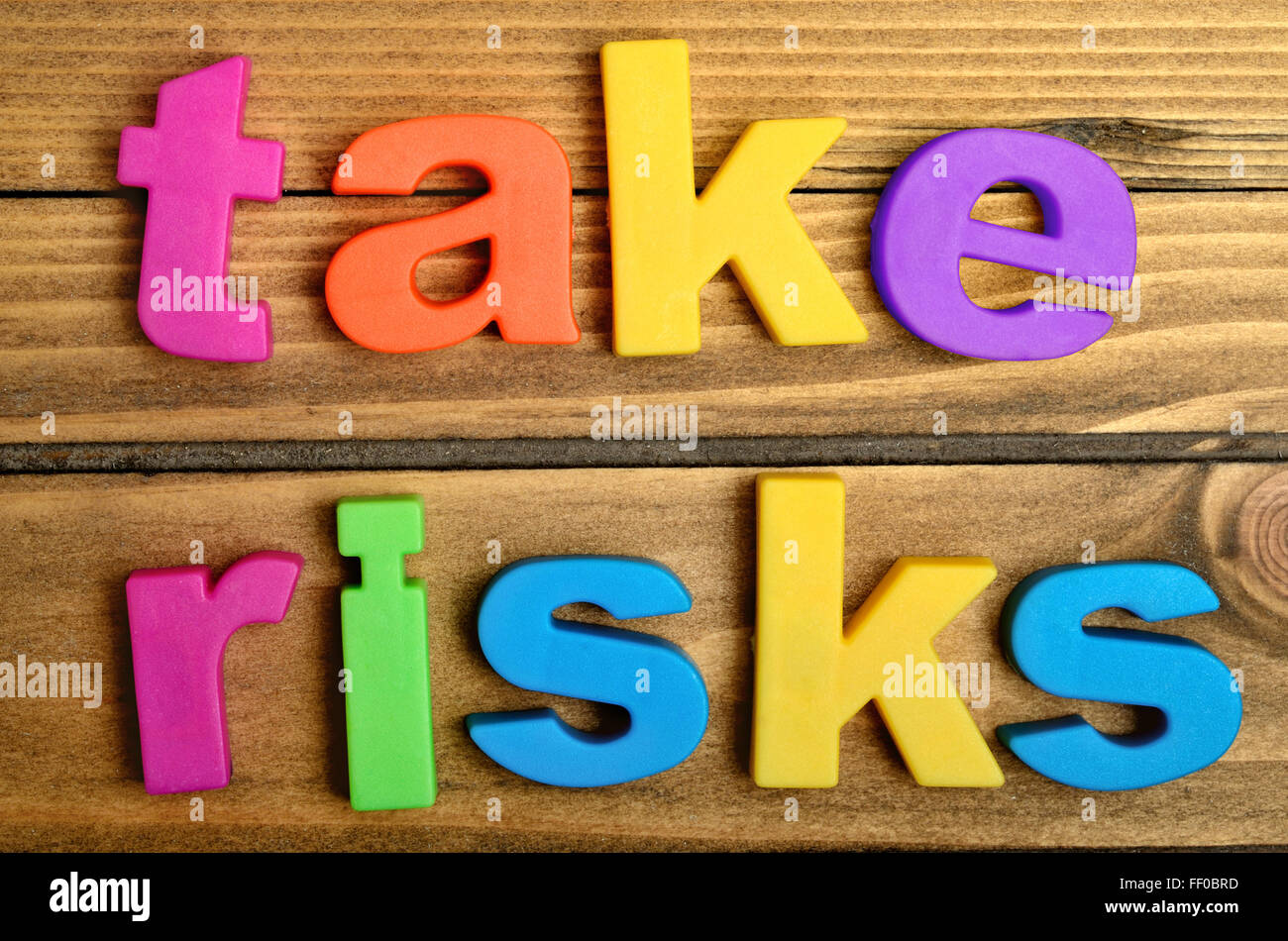 Take risks word on wooden table - Stock Image