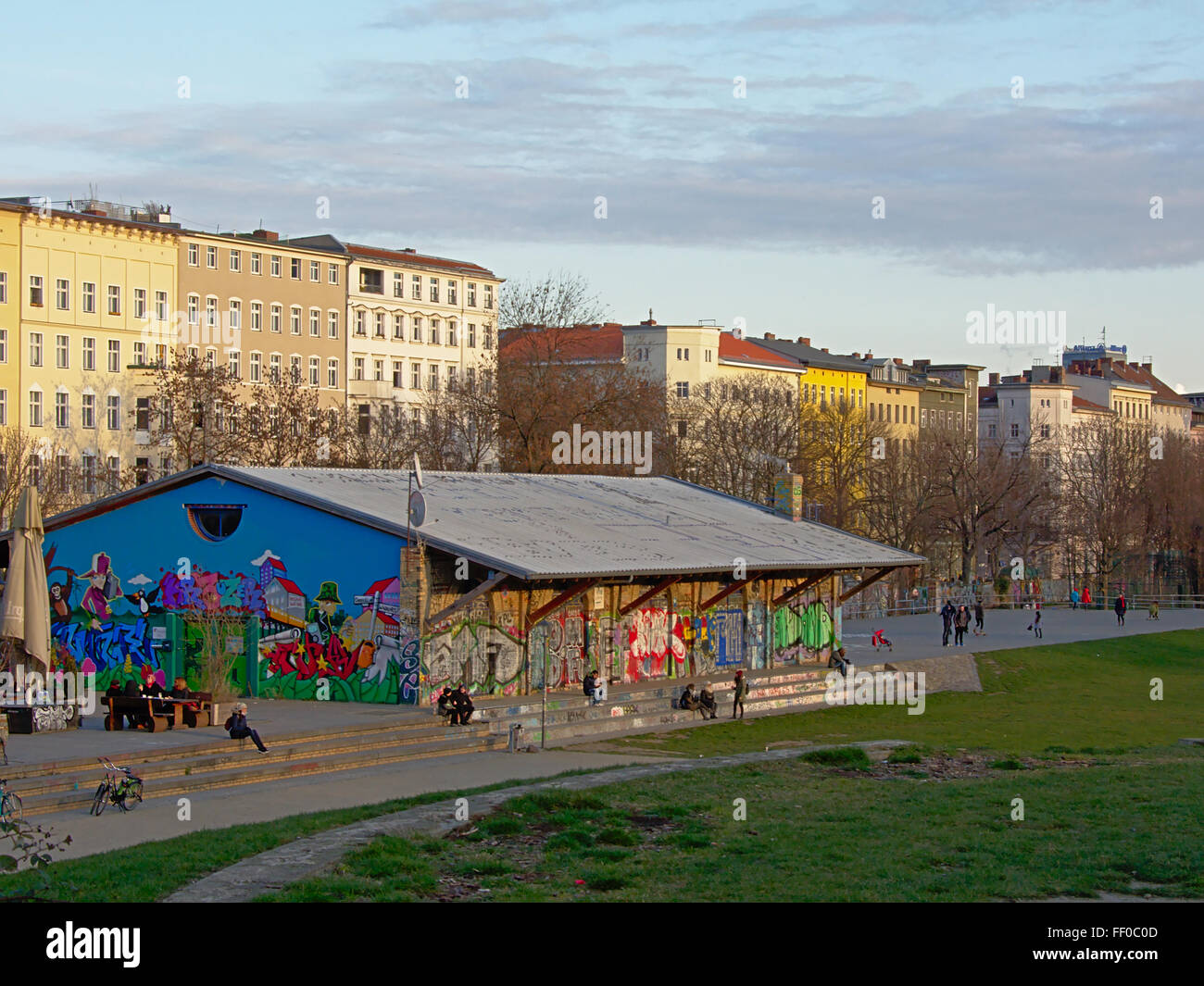 People hanging out around an old railway hangar with colourful graffiti at Görlitzerparc, Berlin Stock Photo