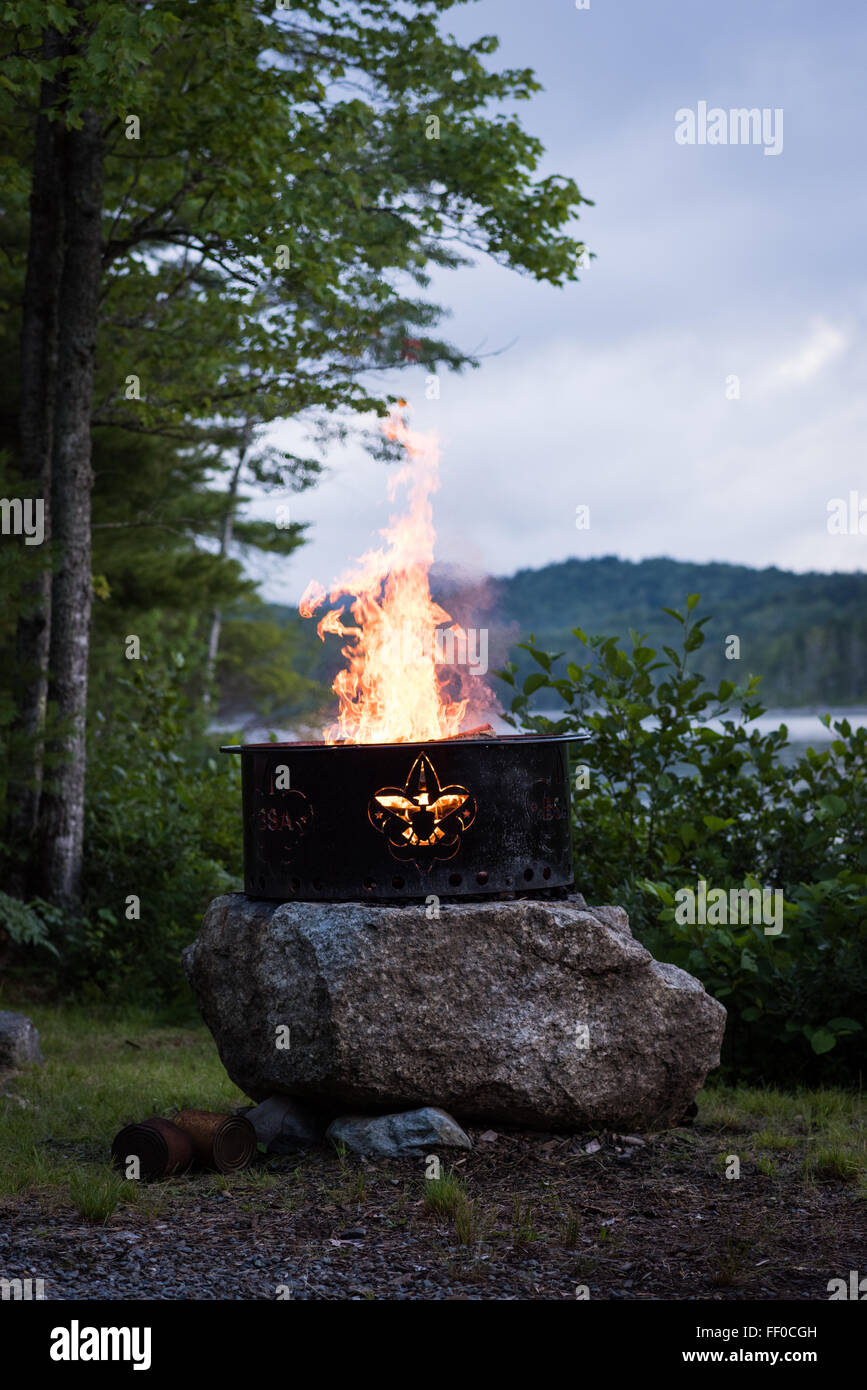 A campfire burns in a fire ring with a Boy Scout's symbol cutout perched on a rock with a lake in the background. - Stock Image