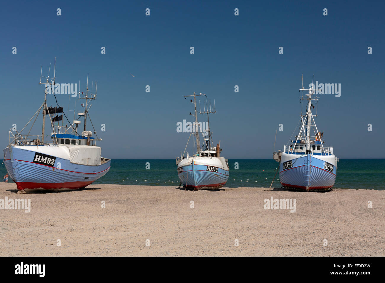 Boats are pulled from the water on their reinforced keels by tractors to sit on the shore, thus being safe from - Stock Image