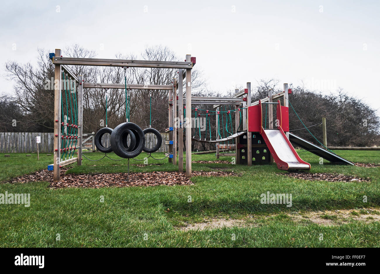 Motor vehicle tyres used as swings in children's playground. - Stock Image