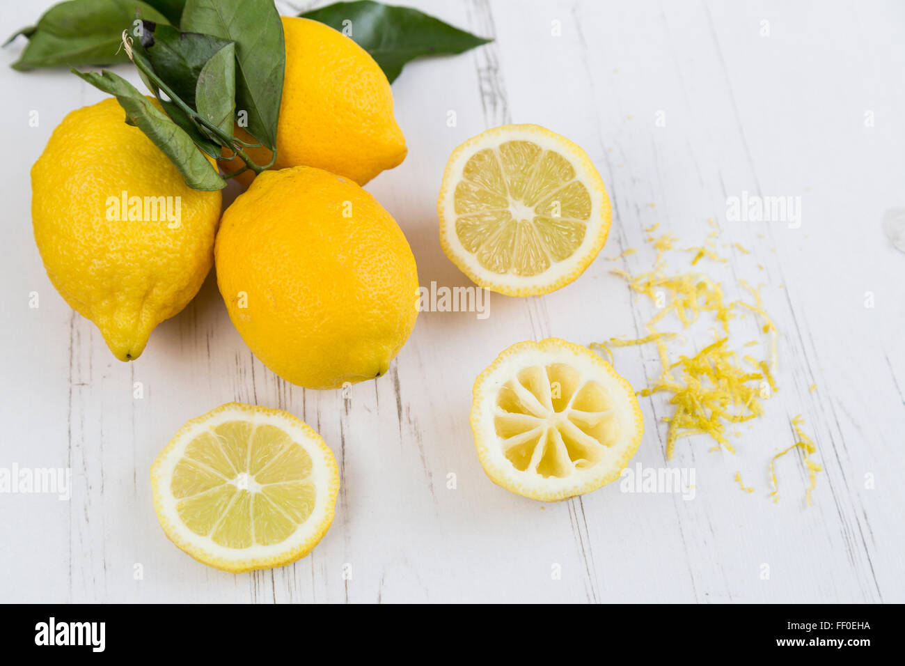 Lemons, slices and zest on a white table - Stock Image