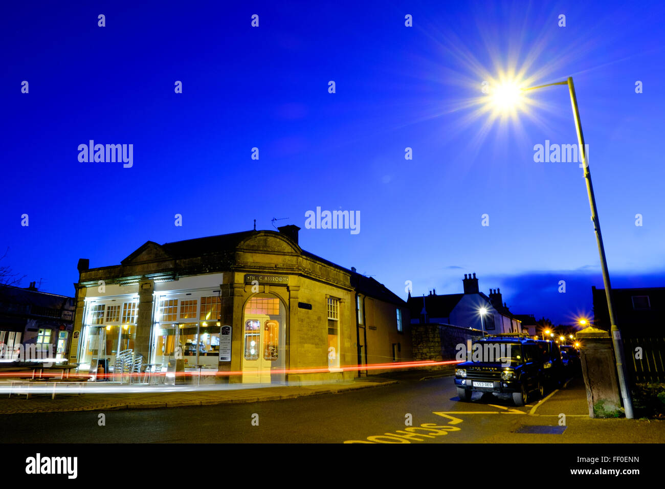 A night photograph of The Classroom Restaurant with a streetlight and car lights in Nairn. - Stock Image
