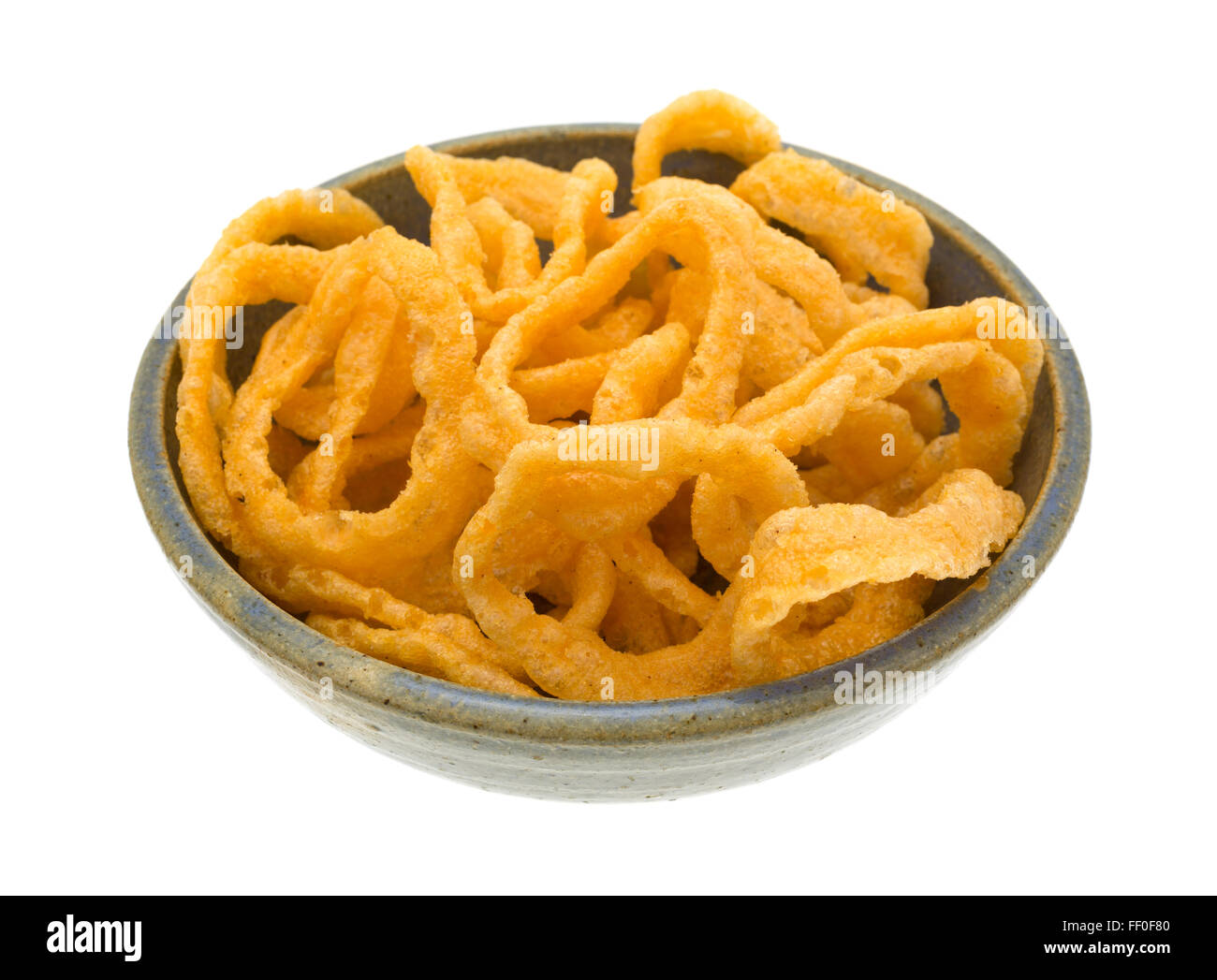 Side view of a large serving of crunchy onion rings in an old stoneware bowl isolated on a white background. - Stock Image