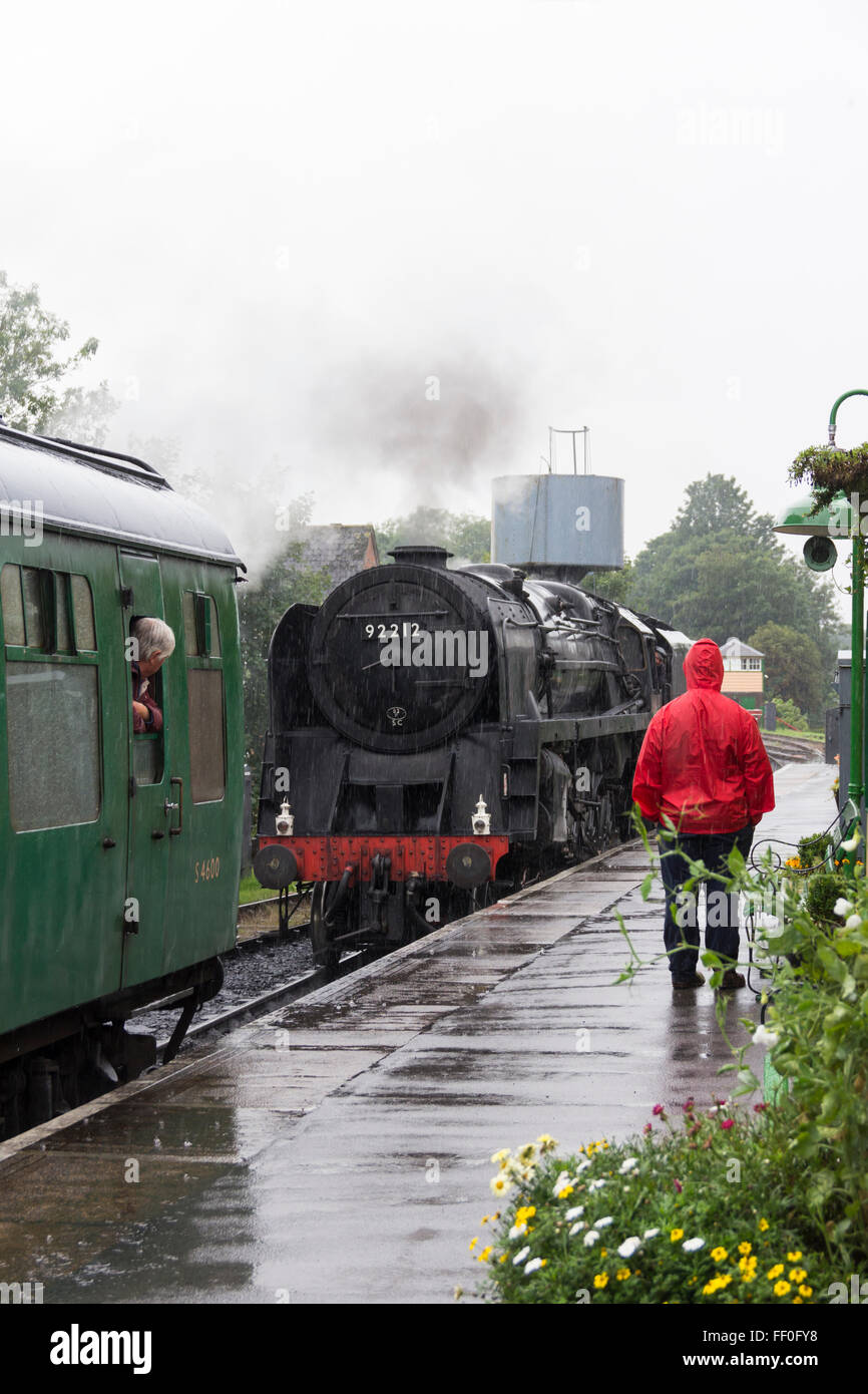 A keen train enthusiast stands in the heavy rain watching Class 9F steam engine 92212 move towards its train at - Stock Image
