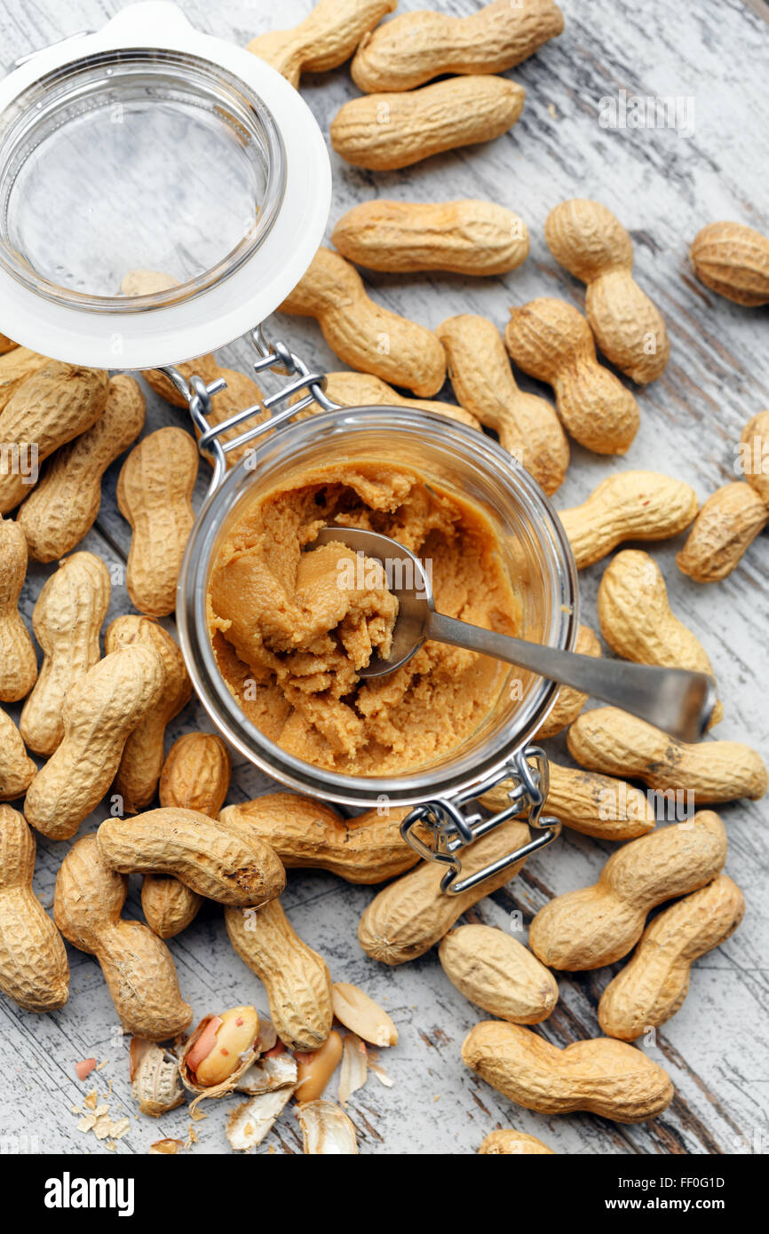 Homemade peanuts butter in a glass jar - Stock Image
